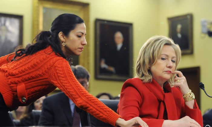Then Secretary of State Hillary Clinton (R) receives a note from her aide Huma Abedin (L) as she testifies about the State Department's budget during a hearing of the State, Foreign Operations and Related Programs Subcommittee of the House Appropriations Committee on March 10, 2011. (Jonathan Ernst/Getty Images)