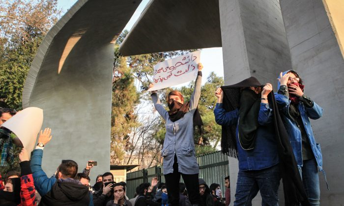 """Students protest the Iranian regime at the University of Tehran on Dec. 30, 2017. One of the students is holding a sign in Persian, which translates to, """"Students would rather die than accept oppression."""" (STR/AFP/Getty Images)"""