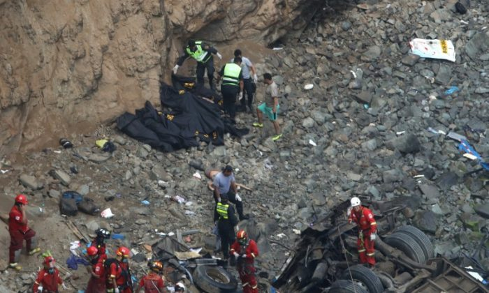 Rescue workers and police work at the scene after a bus crashed with a truck and careened off a cliff along a sharply curving highway north of Lima, Peru, Jan. 2, 2018. (Reuters/Guadalupe Pardo)