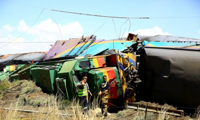 Workers stand next to a wreckage after a train crash near Hennenman in the Free State province, South Africa, January 4, 2018. (REUTERS/Stringer)