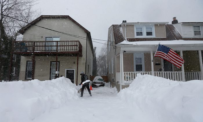 Devery East shovels snow from his driveway in Baltimore, Maryland on Jan. 23, 2016. (Photo by Rob Carr/Getty Images)