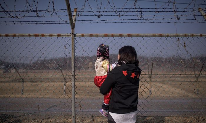 A woman holding a child look towards North Korea as they stand at a military fence at Imjingak park, south of the Military Demarcation Line and Demilitarized Zone (DMZ) separating North and South Korea, on February 19, 2015. South Korean families separated during the Korean war often visit the DMZ to offer prayers to their relatives in the North, on the occasion of the Lunar New Year. (Ed Jones/AFP/Getty Images)