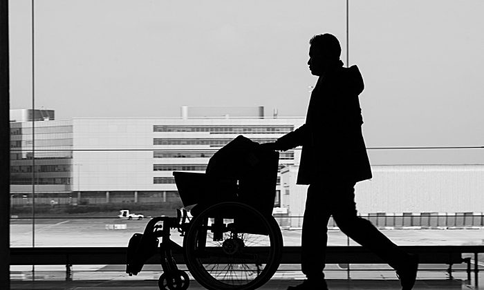 """A woman was denied pre-booked assistance at a UK airport on grounds that she didn't """"look sick"""" enough. The feature image (not directly related) shows a man pushing a wheelchair at what appears to be an airport. (Pixabay / CC0)"""