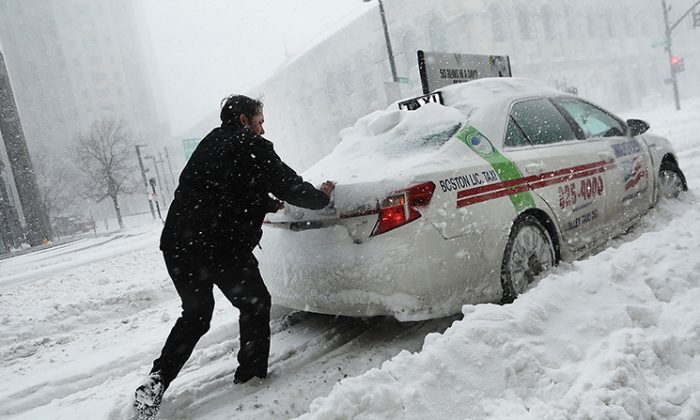 A man pushes a taxi car in the streets of Boston as snow falls from a massive winter storm on Jan. 4, 2018. (Spencer Platt/Getty Images)