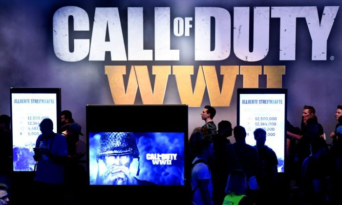 """Visitors wait at the stand of the computer game """"Call of Duty"""" during the gaming fair """"gamescom"""" in Cologne, western Germany on Aug. 22, 2017. (Patrik Stollarz/AFP/Getty Images)"""