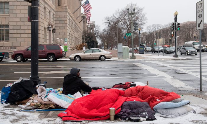 A homeless man sits on a steam grate for warmth alongside the National Mall during a snow storm in Washington, DC, Jan. 4, 2018. (Saul Loeb/AFP/Getty Images)