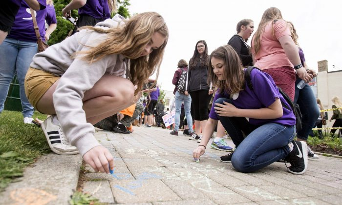 College Avenue Secondary School students write their names on the sidewalk in Museum Square during a rally in Woodstock, Ont., after they and hundreds of their classmates walked out of school on June 7, 2016, to raise awareness of a suicide crisis that was gripping the small Ontario community. (The Canadian Press/ Geoff Robins)