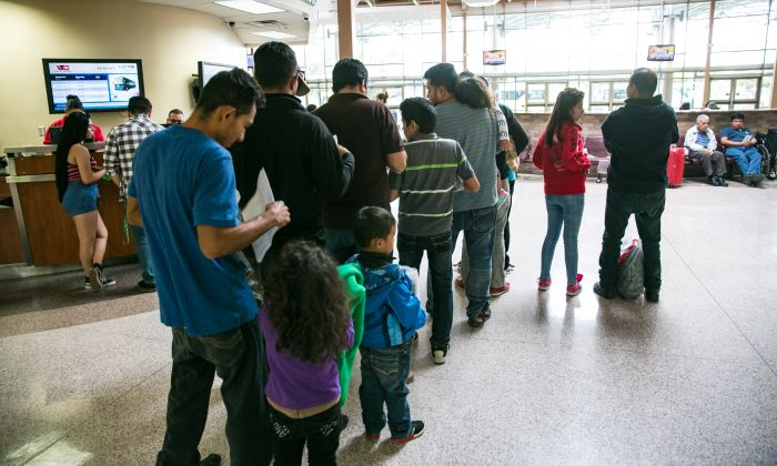 Asylum seekers, mostly from El Salvador, wait in line to purchase bus tickets in McAllen, Texas, on May 30, 2017. (Benjamin Chasteen/The Epoch Times)