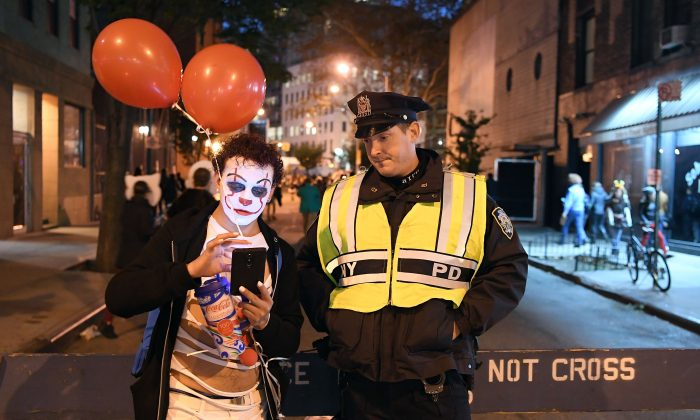 A man dressed in a clown costume talks to an NYPD officer during the 44rd Annual Halloween Parade in New York on Oct. 31, 2017.  (ANGELA WEISS/AFP/Getty Images)