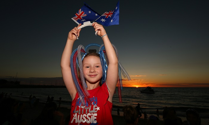 """A young girl proudly displays Australian flags as the sun sets at Bathers Beach on Jan. 26, 2017 in Fremantle, Australia. Fremantle Council held an alternative celebration on Jan. 28, following growing """"political correctness."""" Local Fremantle businesses raised the money to hold the traditional Australia Day fireworks on the 26th despite the Council's decision. Australia Day, formerly known as Foundation Day, is the official national day of Australia and is celebrated annually on Jan. 26 to commemorate the arrival of the First Fleet to Sydney in 1788. (Paul Kane/Getty Images)"""