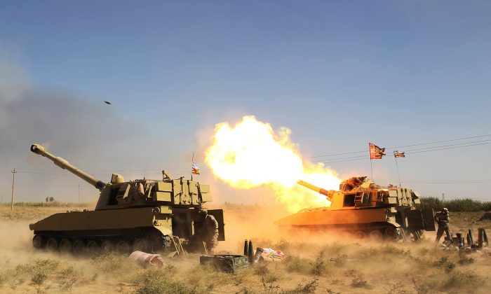 Iraqi forces, backed by the Hashed al-Shaabi (Popular Mobilisation units), fire artillery from a position near the ISIS group's stronghold of Hawija, during an operation to recapture the town from the jihadists on Oct. 4, 2017. (Ahmad Al-Rubaye/AFP/Getty Images)