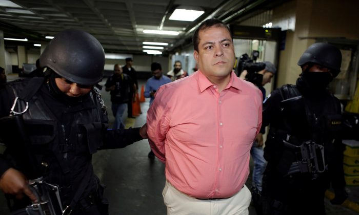 Congressman Julio Juarez Ramirez, who is accused of plotting the murders of two journalists in 2015, is escorted by police officers while arriving to the court in Guatemala City, Guatemala, Jan. 13, 2018. (Reuters/Luis Echeverria)