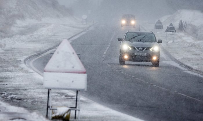 Vehicles drive along the road at the base of Pont ar Daf in the Brecon Beacons as snow begins to fall on Jan. 12, 2017 at Pen Y Fan, Wales. The Met Office has issued a yellow be aware warning for much of the country, as snow and high winds are expected to cause disruption until late on Friday. (Matt Cardy/Getty Images)