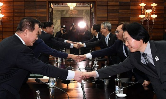 In this Jan. 15, 2018, handout image provided by the South Korean Unification Ministry, South Korean delegation (R) shakes hands with North Korean delegation (L) for their meeting in Panmunjom, North Korea. (South Korean Unification Ministry via Getty Images)