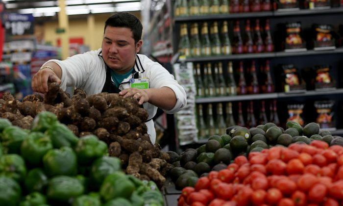 Walmart employee Dayngel Fernandez works in the produce department stocking shelves at a Walmart store in Miami, Florida on February 19, 2015. Walmart announced that it would increase the minimum wage for its workers to $11 after the passage of tax reform bill. (Joe Raedle/Getty Images)