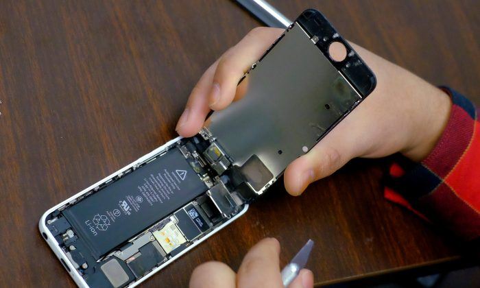 A battery is exposed as a man tries to repair an iPhone in a repair store in New York on Feb. 17, 2016.   (Reuters/Eduardo Munoz/File Photo}