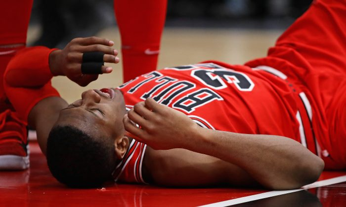 Kris Dunn No. 32 of the Chicago Bulls lays on the floor after suffering a mouth injury following a dunk against the Golden State Warriors at the United Center in Chicago, Ill., Jan. 17, 2018. (Jonathan Daniel/Getty Images)