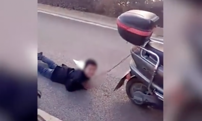 A mother in China's Yunnan Province allegedly tied her son up by the hands and dragged him behind her scooter as a punishment. (火龙果传媒工作室/Youku)