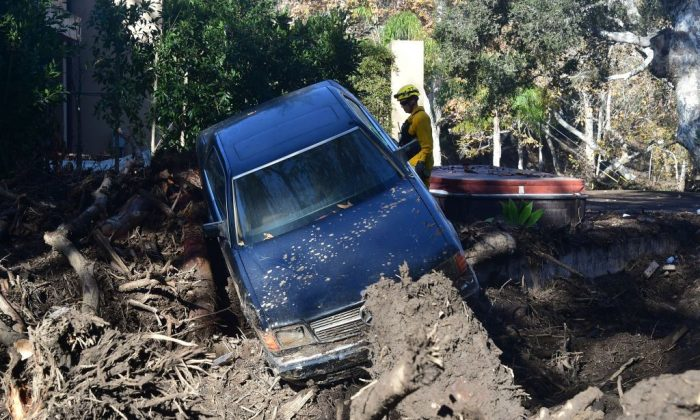 A firefighter stands near a car caught up in a mud slide in Montecito, California Jan. 12, 2018.