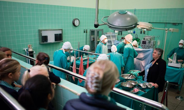Schoolchildren watch a reproduction of an operating theater, Nov. 23, 2017. (Rodger Bosch/AFP/Getty Images)