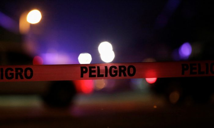 """A police cordon reading """"Danger"""" is pictured at a crime scene where unknown assailants gunned down people at a garage in Ciudad Juarez, Mexico, Jan. 4, 2018. (Reuters/Jose Luis Gonzalez)"""
