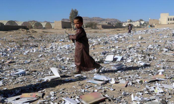 A boy holds a book as he walks on books scattered on the ground after an air strike hit a school book storage building in the northwestern city of Saada, Yemen Jan. 13, 2018. (Reuters/Naif Rahma)