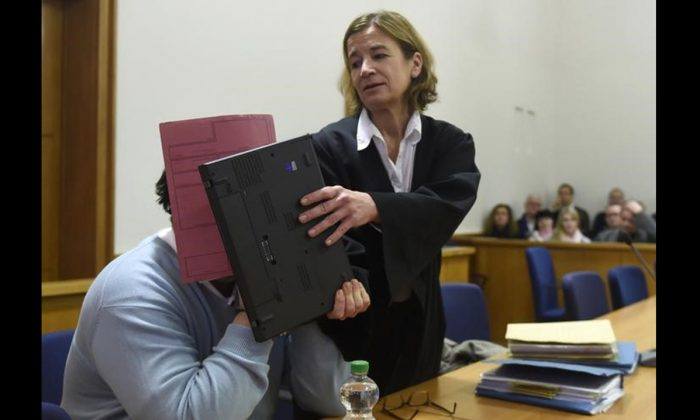 In this file photo,  former nurse Niels H. (L) masks his face with a folder with the help of his lawyer Ulrike Baumann on his arrival in the courtroom at the regional court in Oldenburg, December 9, 2014. (REUTERS/Fabian Bimmer)