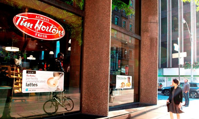 A woman walks past a Tim Hortons coffee shop in Toronto. (The Canadian Press/Doug Ives)