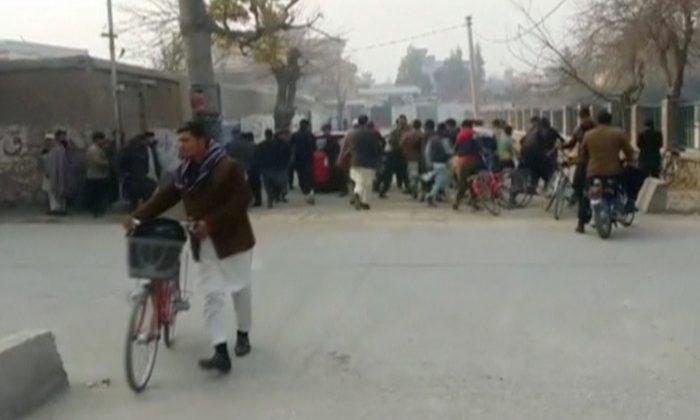 People run away from a site of a blast near the office of the Save the Children aid agency in Jalalabad, Afghanistan, in this still image taken from Reuters TV footage, Jan. 24, 2018. (Reuters/ReutersTV)
