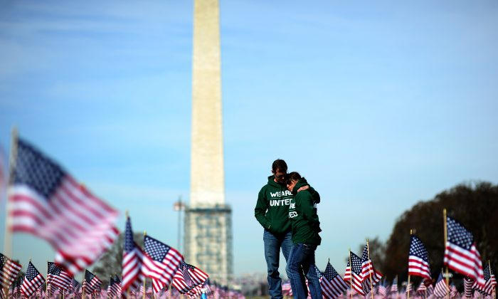 """Iraq war veteran couple Colleen Ryan and Jeff Hensley of the U.S. Navy comfort each other as they help set up 1,892 American flags on the National Mall in Washington, DC, on March 27, 2014. The Iraq and Afghanistan veterans installed the flags to represent the 1,892 veterans and service members who committed suicide this year as part of the """"We've Got Your Back: IAVA's Campaign to Combat Suicide.""""   (JEWEL SAMAD/AFP/Getty Images)"""