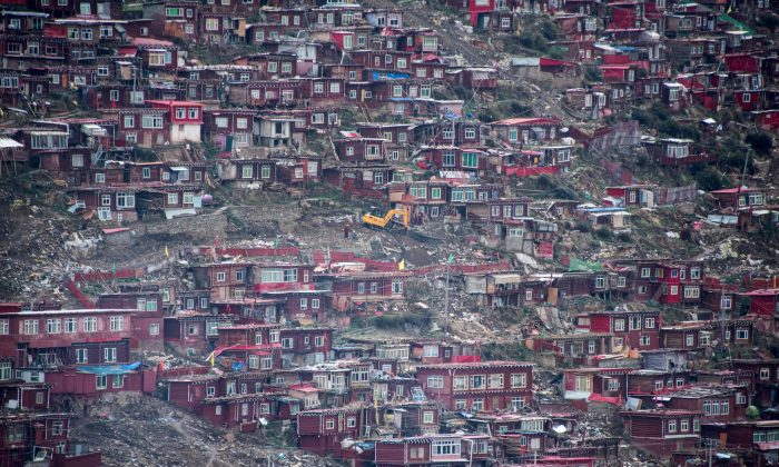 An excavator digging in the debris of partially demolished houses at the Larung Gar Buddhist Academy in Sertar County in southwest China's Sichuan Province, on May 29, 2017. (Johannes Eisele/AFP/Getty Images)