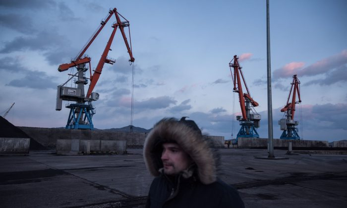 A photo taken on Nov. 21, 2017 shows a Russian worker walking before cranes at the RasonConTrans coal port at Rajin harbour in the Rason Special Economic Zone. (Ed Jones/AFP/Getty Images)