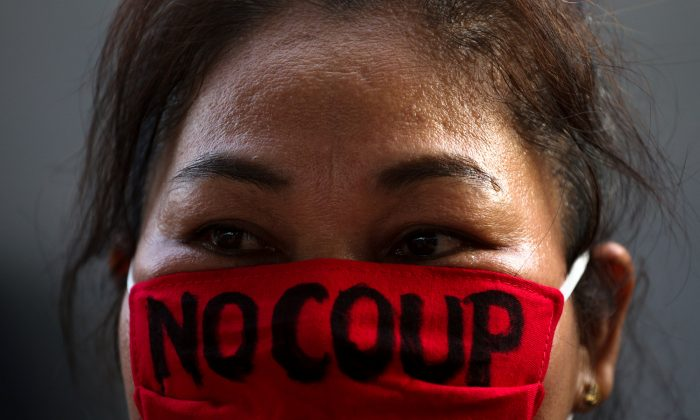 A pro-democracy protester wearing the face mask with a written message, takes part in a protest against junta delaying polls in Bangkok, Thailand Jan. 27, 2018. (Reuters/Athit Perawongmetha)