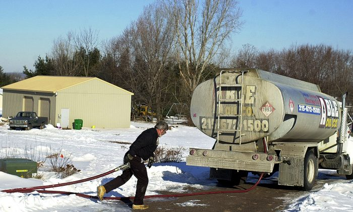 An oil delivery man pulls the oil hose back to his truck after delivering oil to a home February 14, 2003 in Hilltown, Pennsylvania. (William Thomas Cain/Getty Images)