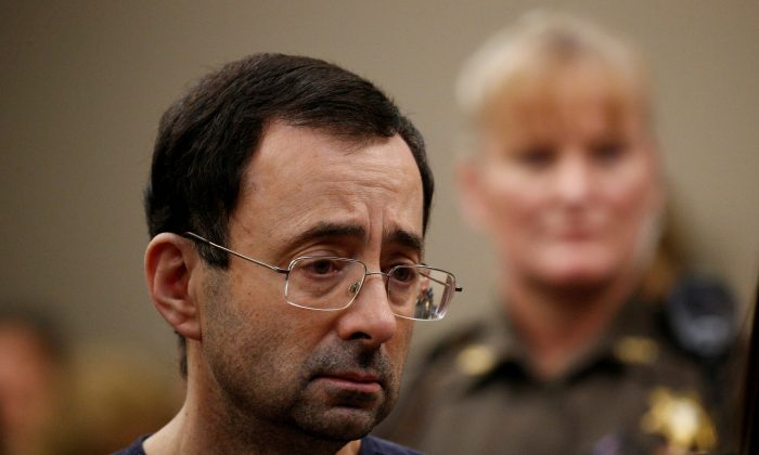 Larry Nassar, a former team USA Gymnastics doctor who pleaded guilty in Nov. 2017 to sexual assault charges, stands with his legal team during his sentencing hearing in Lansing, Michigan, U.S., Jan. 24, 2018. (Reuters/Brendan McDermid)