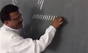 Teacher draws a row of lines on the blackboard and then joins them to make a cursive alphabet