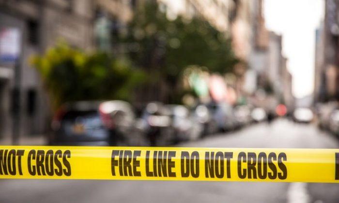 Police tape blocks a street. (Benjamin Chasteen/The Epoch Times)