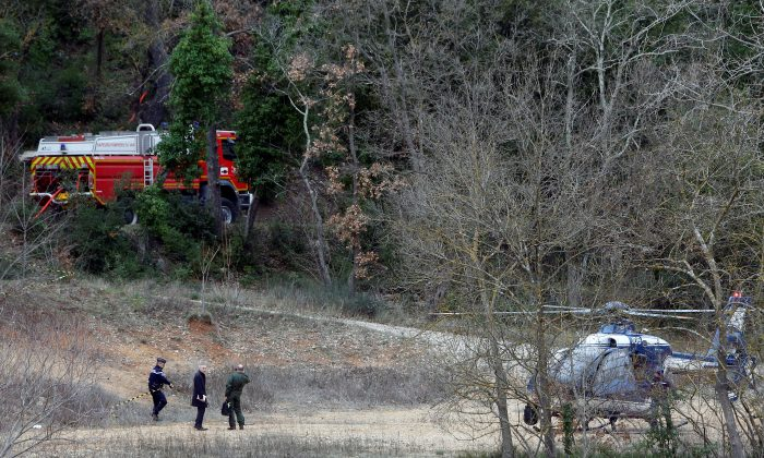 A gendarme secures an area near the site where two French military helicopters belonging to an army flight training school crashed killing five people near the Lac de Carces in the southeastern Var region, France, Feb. 2, 2018. (Reuters/Jean-Paul Pelissier)