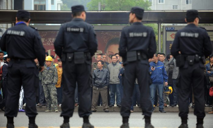 Citizens watch as police stand guard outside the Xianning Intermediate People's Court in Xianning City, central China's Hubei Province, on March 31, 2014. (STR/AFP/Getty Images)