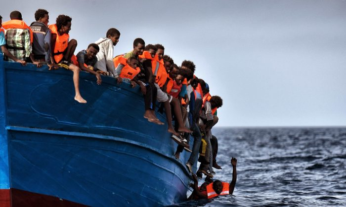Migrants wait to be rescued as they drift in the Mediterranean Sea some 20 nautical miles north off the coast of Libya on Oct. 3, 2016. (Aris Messinis/AFP/Getty Images)