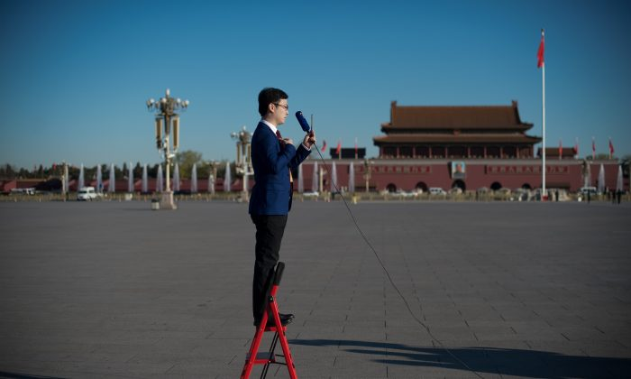 A television journalist stands on a ladder as he reports in Tiananmen Square in Beijing on March 13, 2017. (Nicolas Asfouri/AFP/Getty Images)