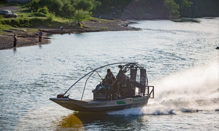 U.S. Customs and Border Protection agents monitor the Rio Grande on a boat between the Mexican city of Ciudad Miguel Aleman (far side) and the Texan city of Roma, on May 31, 2017. (Benjamin Chasteen/The Epoch Times)