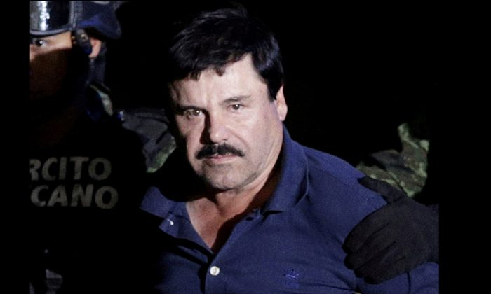 """In this file photo, recaptured drug lord Joaquin """"El Chapo"""" Guzman is escorted by soldiers at the hangar belonging to the office of the Attorney General in Mexico City, Mexico Jan 8, 2016. (REUTERS/Henry Romero)"""