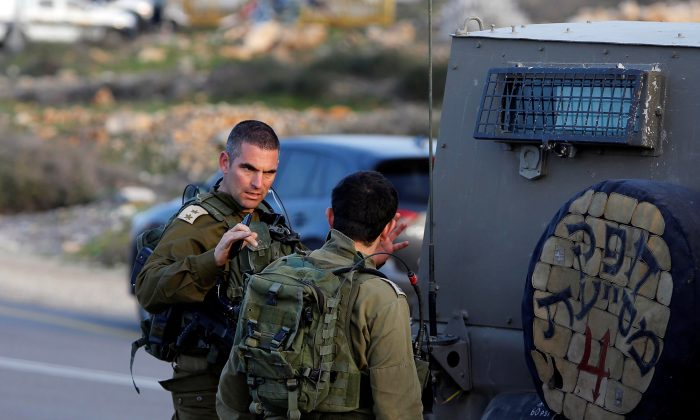 An Israeli soldier gestures as he stands near the scene of a stabbing attack north of Hebron, in the occupied West Bank, Feb. 7, 2018. (Reuters/Mussa Qawasma)