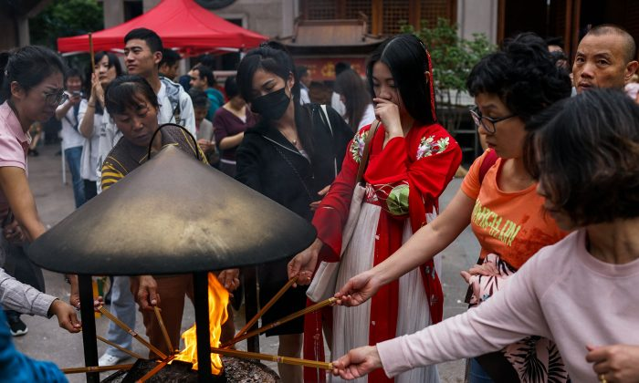 Chinese people burn incense sticks during the mid-autumn festival at the Jing'an Temple in Shanghai on Oct. 4, 2017. (Chandan Khanna/AFP/Getty Images)