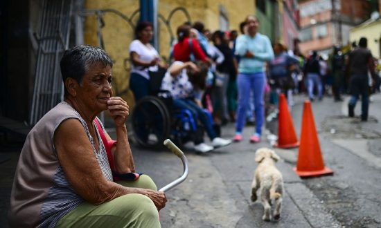 An elderly woman lines up to buy basic food and household items outside a supermarket in the poor neighborhood of Lidice, in Caracas, Venezuela on May 27, 2016. (RONALDO SCHEMIDT/AFP/Getty Images)