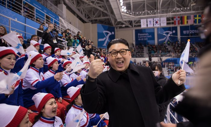 A man impersonating North Korean dictator Kim Jong Un gestures as he stands before North Korean cheerleaders attending the Unified Korean ice hockey game against Japan during the Pyeongchang 2018 Winter Olympic Games at the Kwandong Hockey Centre in Gangneung on Feb. 14, 2018. (YELIM LEE/AFP/Getty Images)