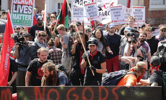 Protesters, including members of the communist extremist group Antifa, hold signs during an Aug. 12, 2017, protest in Charlottesville, Va. According to a new book, social conflicts are being used by special interest groups and governments to shape narratives and alter public perception. (Chip Somodevilla/Getty Images)