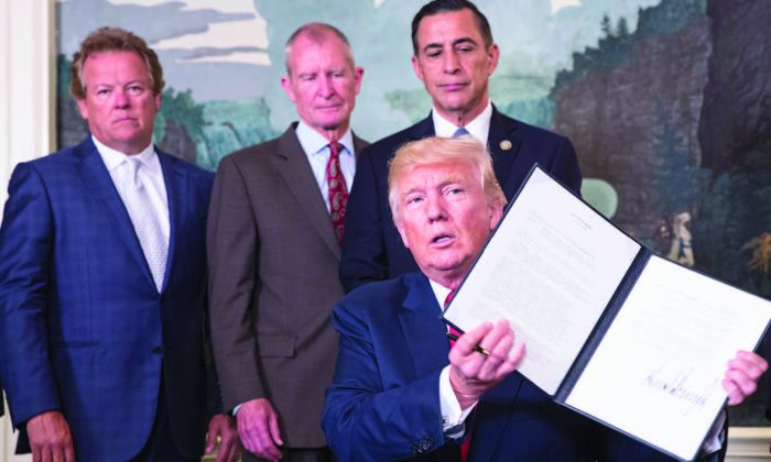President Donald Trump holds a memorandum on tackling China's trade practices, at the White House on Aug. 14, 2017. (CHRIS KLEPONIS-POOL/GETTY IMAGES)