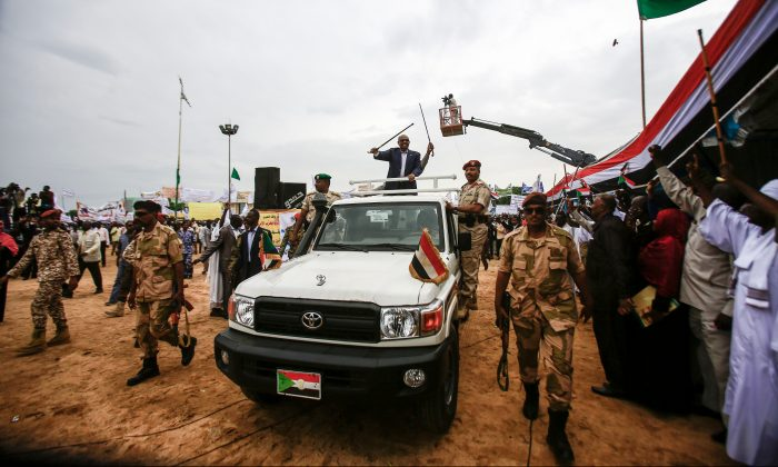 Sudanese President Omar al-Bashir (C) waves a walking stick as he rides in the back of a pickup truck in an advancing motorcade in Nyala, the capital of South Darfur province, on Sept. 21, 2017. (Ashraf Shazly/AFP/Getty Images)